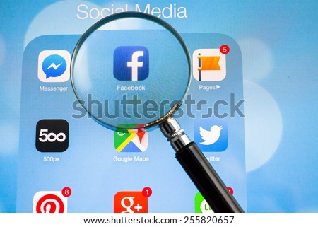 BANGKOK FEBRUARY 26, 2015: Facebook being magnified on tablet. Facebook is an online social networking service headquartered in Menlo Park, California. - stock photo