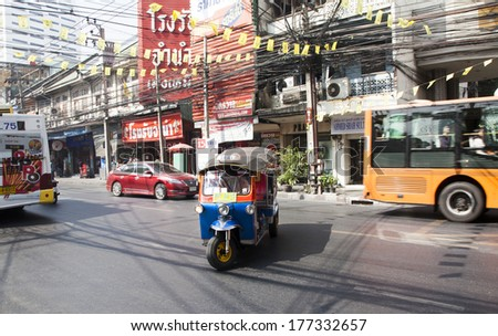 BANGKOK - JAN 24: A three wheeled tuk tuk taxi on a street in the Thai capital on Jan 24, 2014 in Bangkok, Thailand. Tuk tuks are commonly used in transporting people and goods around the capital.  - stock photo