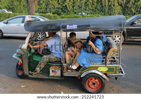 BANGKOK - JAN 20: A tuk tuk taxi transports students on a city centre street on Jan 20, 2011 in Bangkok, Thailand. Tuk tuks are commonly used in transporting people and goods around the capital. - stock photo