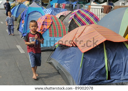 BANGKOK - JAN 20: An unidentified boy walks through a roadside tent village outside Government House during a large yellow-shirt anti-government protest on 20, 2011 in Bangkok, Thailand. - stock photo