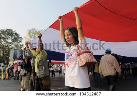 BANGKOK - JAN 25: People's Alliance for Democracy, or yellow-shirts, protest under a Thai flag near Government House while attending an ant-government rally on Jan 25, 2011 in Bangkok, Thailand. - stock photo