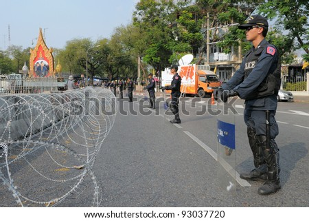 BANGKOK - JAN 25: Riot police behind razor wire guard Government House as yellow-shirt protesters hold a large rally Jan 25, 2011 in Bangkok, Thailand. - stock photo