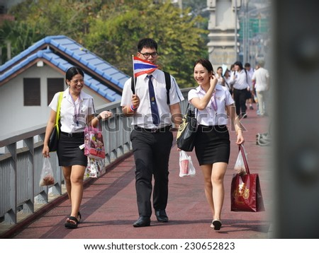 BANGKOK - JAN 7: Unidentified Thai university students in uniform walk along a street on Jan 7, 2014 in Bangkok, Thailand. The wearing of uniforms is compulsory at many of the country's universities. - stock photo