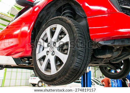 Bangkok january 14,2015 Red Car on the elevator to wait for the check and wait for change tires for safe driving. - stock photo