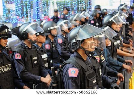 BANGKOK - JANUARY 9: Riot police block an entrance to Sukumvit Road at a 30,000 strong anti government Red Shirt protest at Rachaprasong junction on January 9, 2011 in Bangkok, Thailand. - stock photo