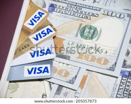 BANGKOK - JUL 14, 2014 : Photo of VISA credit card on banknote. VISA is an American multinational financial services corporation - stock photo