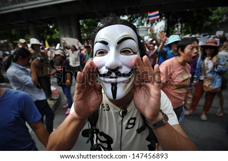 BANGKOK - JULY 21: A masked protester shouts anti-government slogans while attending a rally on July 21, 2013 in Bangkok, Thailand. The protesters are calling for the government to be overthrown. - stock photo