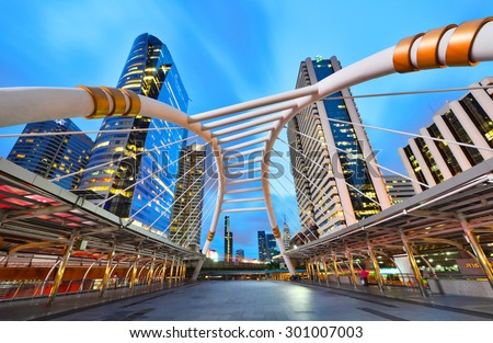 BANGKOK - JULY 28 : Buildings and a skywalk architecture like spider for transit between Sky Transit and Bus Rapid Transit Systems at Sathorn-Narathiwas junction on July 28, 2015 in Bangkok, Thailand. - stock photo