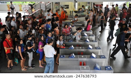 BANGKOK - JUN 1: Travellers pass through a ticket barrier at a city centre BTS Skytrain station on Jun 1, 2013 in Bangkok, Thailand. The Thai capital's rail network has a daily ridership of 600,000. - stock photo