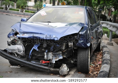 BANGKOK - JUNE 5: A crashed car sits by a roadside on June 5, 2013 in Bangkok, Thailand. According to Dept of Land Transport statistics Bangkok saw 27166 road vehicle accidents between 2011 and 2012. - stock photo