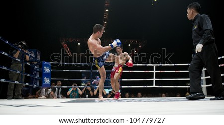 "BANGKOK - JUNE 9: Muay Thai Welterweight World Championship fight - Fabio Pinca (FRA) foot kicking Big Ben Ch. Praram 6 (Thailand) at ""BATTLE FOR THE BELTS"" event on June 9, 2012 in Bangkok, Thailand - stock photo"