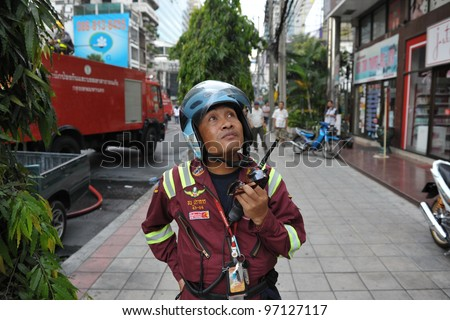 BANGKOK - MAR 5: A firefighter looks on at blaze at Fico Building on Asoke Road in the city centre on Mar 5, 2012 in Bangkok, Thailand. The BMA has launched an investigation in the cause of the blaze. - stock photo