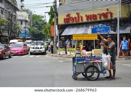 BANGKOK - MAR 27: A vendor looks for customer on a city centre street on MAR 27, 2015 in Bangkok, Thailand. Government statistics indicate 16,000 registered street vendors in the Thai capital. - stock photo