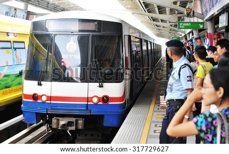 BANGKOK - MAR 19: Passengers wait for an approaching train on a platform at a city centre BTS Skytrain station on Mar 19, 2013 in Bangkok, Thailand. The BTS has a daily ridership of 600,000 people. - stock photo