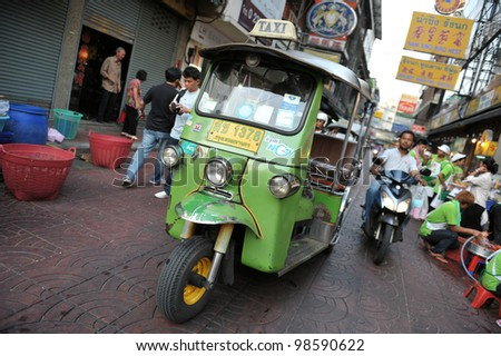 BANGKOK - MARCH 2: A three-wheeled  tuk tuk taxi drives along a road in Chinatown on March 2, 2012 in Bangkok, Thailand. Tuk tuks can be hired from as little as $1 or B30 a fare for shop trips. - stock photo
