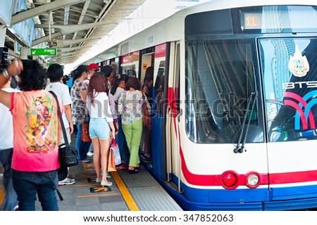 BANGKOK - MARCH 17, 2013: People board a BTS Skytrain at a city centre station. The Thai capital's BTS rail public transport system serves 600,000 passengers daily. - stock photo