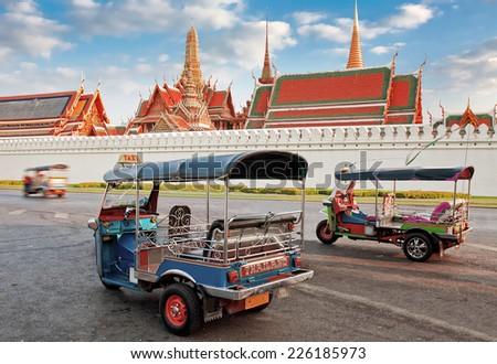 BANGKOK - MARCH 3: Tuk Tuk taxi waiting customers about Wat Phra Kaeo, Temple of Emerald Buddha and home of Thai King in Bangkok, Thailand, March 3, 2014. - stock photo