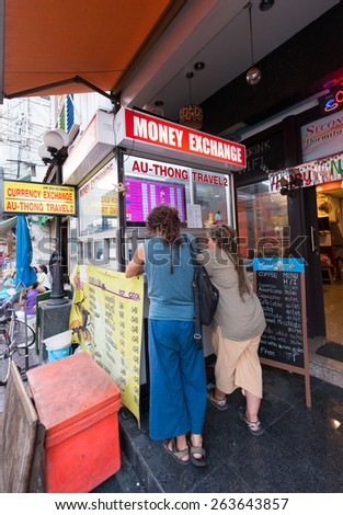 BANGKOK - MARCH 9, 2015: Unidentified tourists exchange money in Sam Sen Road, in Khao San Road area where lots of budget hotels and guesthouses are located. - stock photo