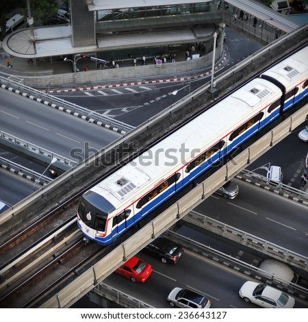 BANGKOK - MAY 11: Aerial view of a BTS Skytrain on elevated rails in the city centre on May 11, 2012 in Bangkok, Thailand. Each train of the mass transport network can carry over 1,000 passengers.  - stock photo