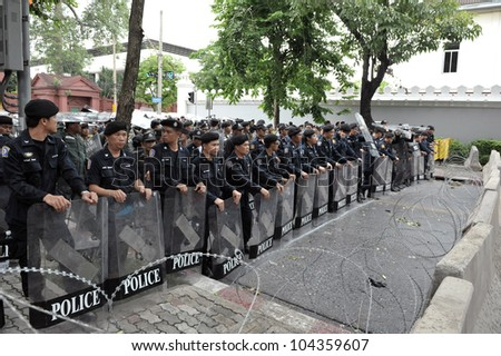 BANGKOK - MAY 31: Policemen stand guard at a barricade during an anti-goverment People's Alliance for Democracy, or yellow-shirt, rally outside Parliament on May 31, 2012 in Bangkok, Thailand. - stock photo