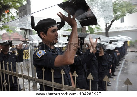 BANGKOK - MAY 31: Policemen use riot shields to shelter from rain during People's Alliance for Democracy, or yellow-shirt, rally outside Parliament on May 31, 2012 in Bangkok, Thailand. - stock photo