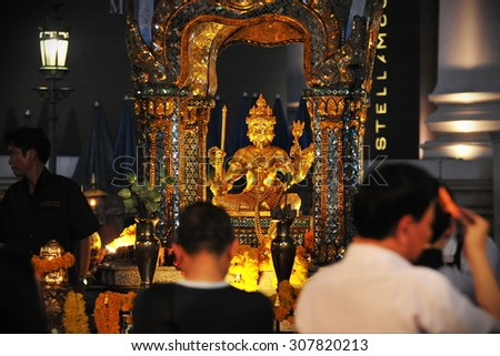 BANGKOK - MAY 24: Temple goers make merit at the Erawan Shrine on May 24, 2013 in Bangkok, Thailand. The city centre shrine was built in 1956 and has become a popular landmark in the Thai capital. - stock photo