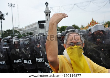BANGKOK - NOV 24: A nationalist protester from Pitak Siam beckons to other protesters to confront riot police while attending a large anti-government rally on Nov 24, 2012 in Bangkok, Thailand. - stock photo