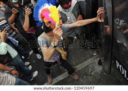 BANGKOK - NOV 24: A protester confronts riot police while participating in an anti-government rally organised by the nationalist Pitak Siam group on Nov 24, 2012 in Bangkok, Thailand. - stock photo