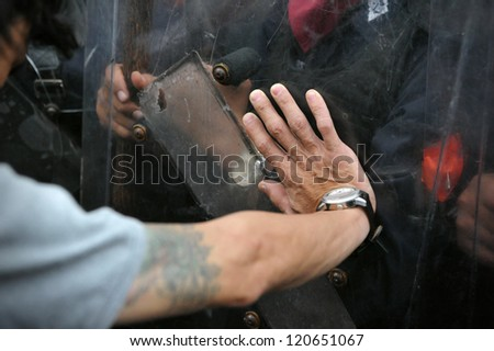 BANGKOK - NOV 24: A protester from the nationalist Pitak Siam group pushes the shield of riot police during a violent anti-government rally with riot police on Nov 24, 2012 in Bangkok, Thailand. - stock photo