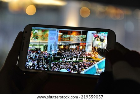 BANGKOK - NOV 7: A protester uses a smartphone to capture an anti-government rally on Nov 7, 2013 in Bangkok, Thailand. The Thai protest movement are calling for the government to be overthrown. - stock photo