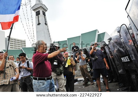 BANGKOK - NOV 24: An unidentified protester from the nationalist Pitak Siam group shouts abuse at a police line during a large anti government rally on Nov 24, 2012 in Bangkok, Thailand.  - stock photo
