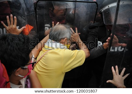 BANGKOK - NOV 24: Nationalist anti-government protesters from Pitak Siam clash with riot police on Makhawan Bridge on Nov 24, 2012 in Bangkok, Thailand. - stock photo