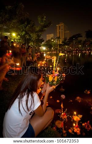BANGKOK - NOVEMBER 21, 2010: A young Buddhist woman prays and makes a wish before launching her krathong during the Thai holiday festival of Loi Krathong on November 21, 2010 in Bangkok - stock photo