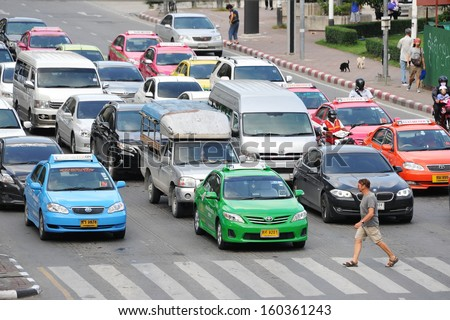 BANGKOK - OCT 1: Traffic waits at a busy junction in the city centre on Oct 1, 2013 in Bangkok, Thailand. Annually an estimated 150,000 new cars join the heavily congested roads of Bangkok. - stock photo