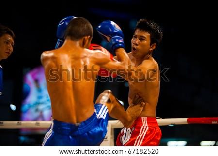 BANGKOK - OCTOBER 12:  A muay thai fighter receives a kick jab to the stomach at Fight Night October 12, 2010 at Bangkok, Thailand - stock photo