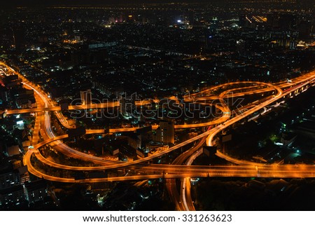 Bangkok's cityscape at night with highrise buildings and a complicated highway interchange, highlighted under the glow of sodium vapor street lamps.  - stock photo