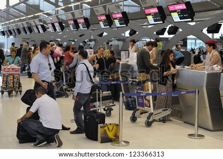 BANGKOK - SEPT 19: Passengers arrive at check-in counters at Suvarnabhumi Airport on Sept 19, 2012 in Bangkok, Thailand. The airport handles 45 million passengers annually. - stock photo