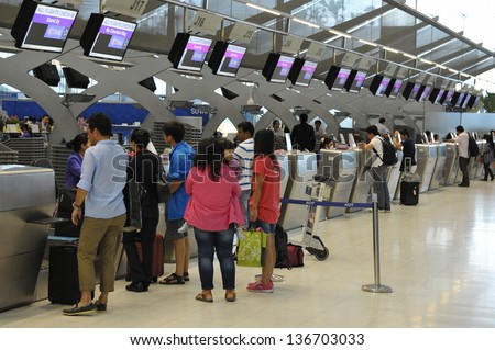 BANGKOK - SEPT19: Passengers arrive at check-in counters at Suvarnabhumi Airport on Sept 19, 2012 in Bangkok, Thailand. The airport is one of the busiest in Asia, handling 45mn travellers annually. - stock photo