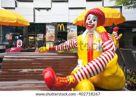 BANGKOK, THAILAND - APRIL 8, 2016 : Portrait of of Ronald-Mcdonald sitting on bench in front of McDonald's restaurant. McDonald's operates in 119 countries with 160 stores in Thailand. Selective Focus - stock photo