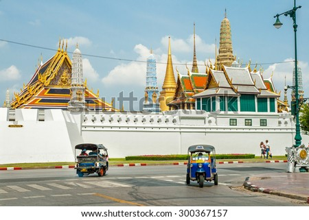 BANGKOK, THAILAND - APRIL 4 : Tricycle taxi of Thailand on street and background of Wat Phra Kaew ( the Temple of the Emerald Buddha) on April 4 , 2008. Here is destinations of landmarks traveler. - stock photo