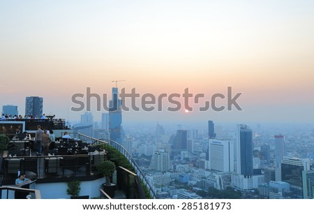 BANGKOK THAILAND - APRIL 20, 2015: Unidentified people watch Bangkok city view from rooftop bar. Bangkok is a capital city and business centre of Thailand.  - stock photo