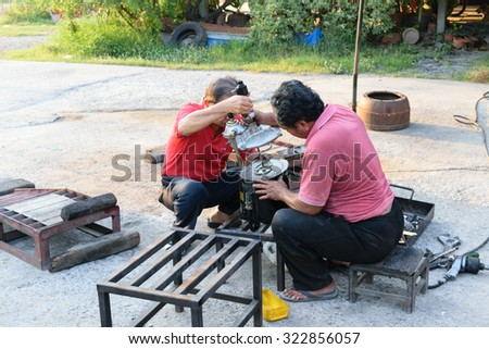 Bangkok, Thailand - April 5, 2015 : Unidentified two workers repair car truck part at garage. - stock photo