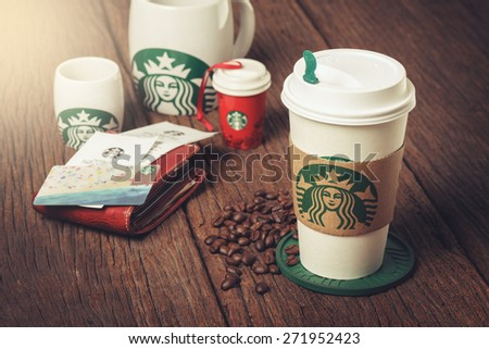 BANGKOK, THAILAND - APRIL 23, 2015: White paper cup and other gift with Starbucks logo. Starbucks is the world's largest coffee house with over 20,000 stores in 61 countries. - stock photo