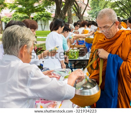 BANGKOK,THAILAND-August 15, 2015: A Lady is putting food offerings into a Buddhist monk's bowl during religious ceremony - stock photo