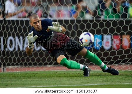 BANGKOK,THAILAND-AUGUST07:Goalkeeper V�­ctor Valdes of FC Barcelona saves the ball during the international friendly match Thailand and FC Barcelona at Rajamangala Stadium on August 7,2013 in,Thailand. - stock photo