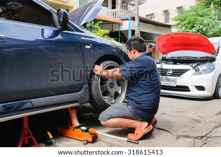 Bangkok, Thailand - August 30, 2015 : Unidentified serviceman checking suspension in a car at garage - stock photo