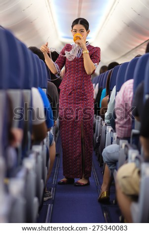 BANGKOK, THAILAND, DECEMBER 29, 2014 : An air hostess of the Thai Lion Air company is showing how to use oxygen mask before taking off from the Suvarnabhum airport in Bangkok, Thailand - stock photo