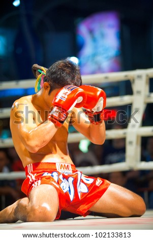 BANGKOK, THAILAND - DECEMBER 8, 2010: An unidentified muay thai kickboxer kneels and prays with his gloves during a pre-fight ritual called the wai khru on December 8, 2010 in Bangkok, Thailand - stock photo