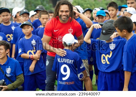 BANGKOK,THAILAND - DECEMBER 04: Christian Karembeu (red)poses with local child at the Global Legends Series coaching clinic, at the Thailand Sports Authority, on December 4, 2014 in Bangkok, Thailand. - stock photo