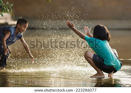 BANGKOK, THAILAND, DECEMBER 25, 2011: Dressed kids spreading water each other in a flooded square near the river in Bangkok, Thailand - stock photo